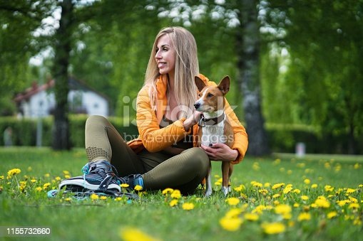 Young pretty woman with her Basenji dog sitting in a meadow. Dandelions can be seen blooming around