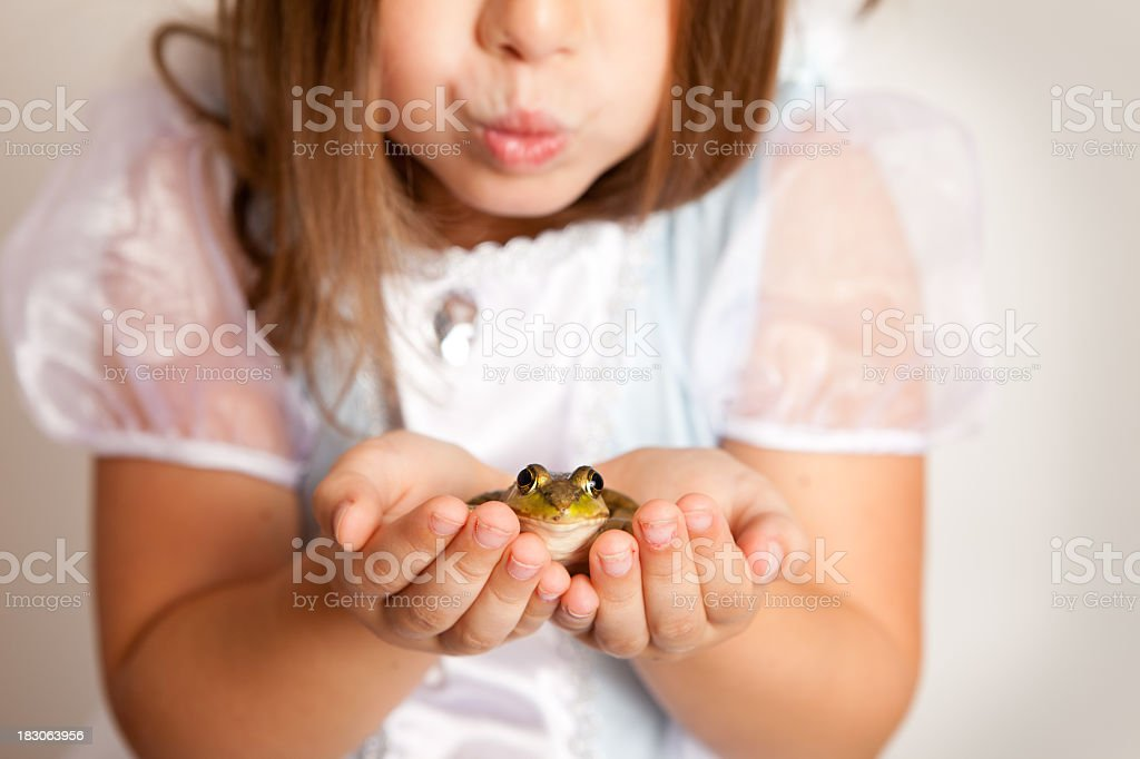 Young Princess Girl about to Kiss a Frog stock photo