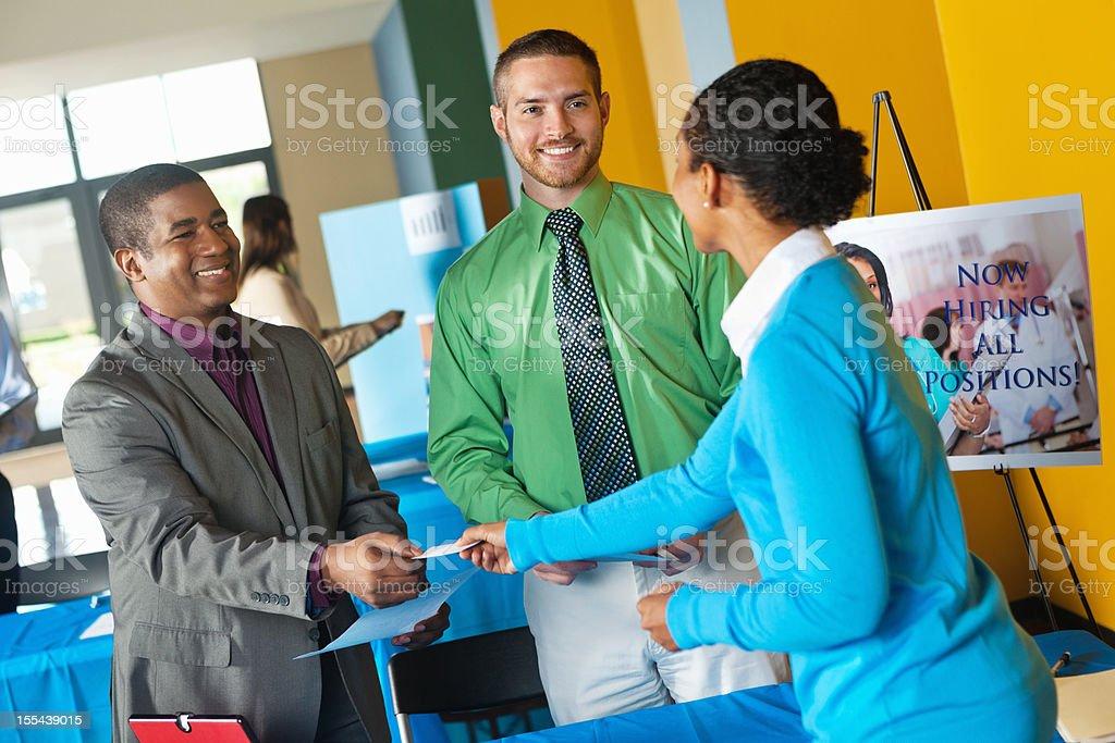 Junge professionelle nimmt business card von team im job fair – Foto