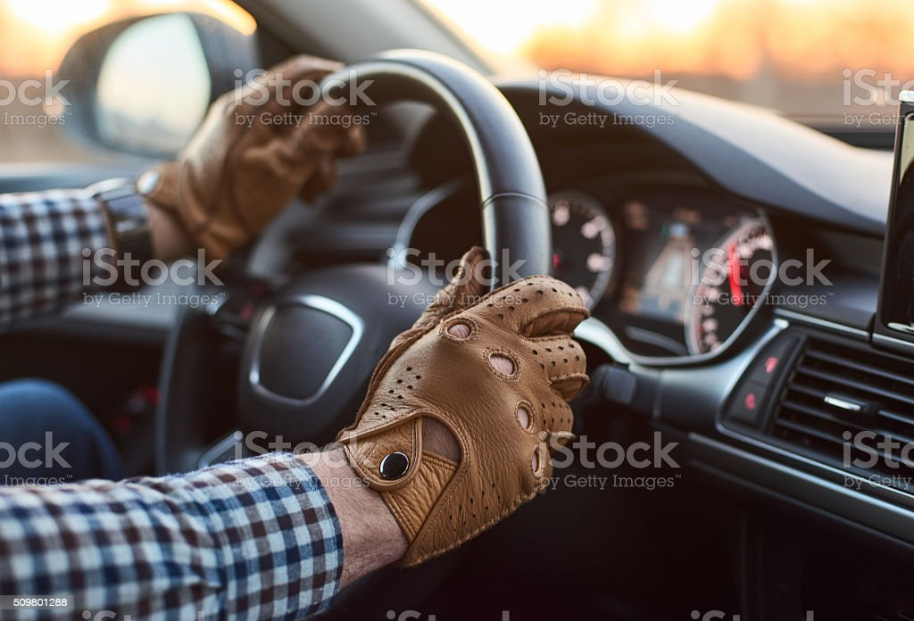 Young professional driver in car with hands on steering wheel stock photo
