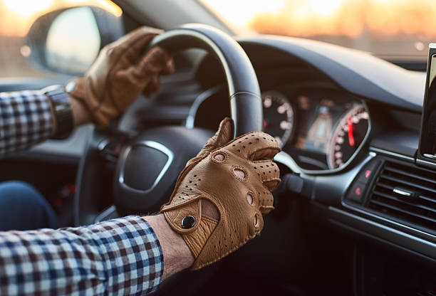 jeune professionnel conducteur dans la voiture avec les mains sur le volant - paire de gants photos et images de collection