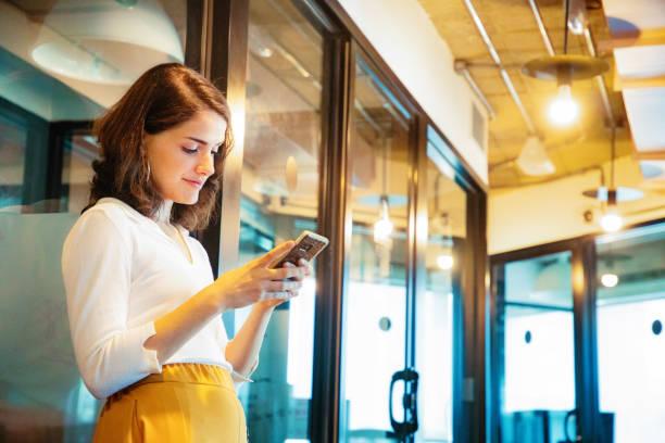 Junge professionelle Büroangestellte liest ihre E-Mails auf ihrem Handy in modernen Bürokorridor – Foto