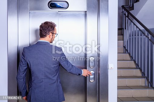 638591126 istock photo Young professional in suit waiting in front of the elevator 1178908241