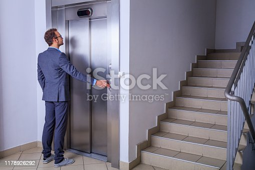 638591126 istock photo Young professional in suit waiting in front of the elevator 1178926292