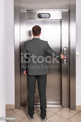 638591126 istock photo Young professional in suit waiting in front of the elevator 1179586647