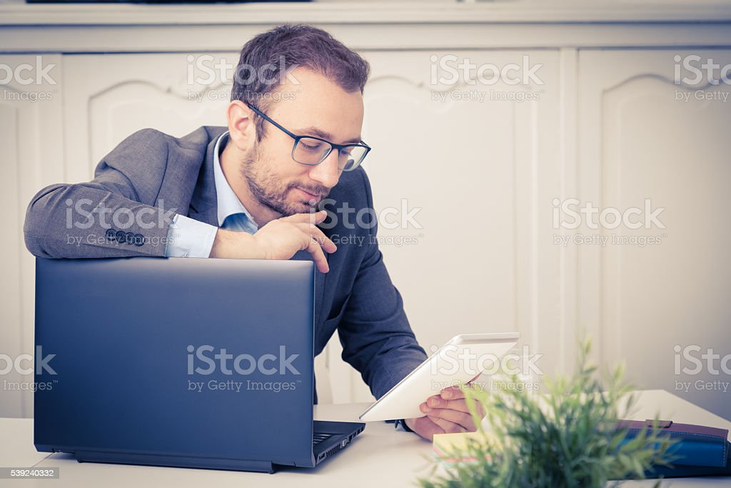 Young professional looking on tablet device and leaning on laptop foto de stock libre de derechos