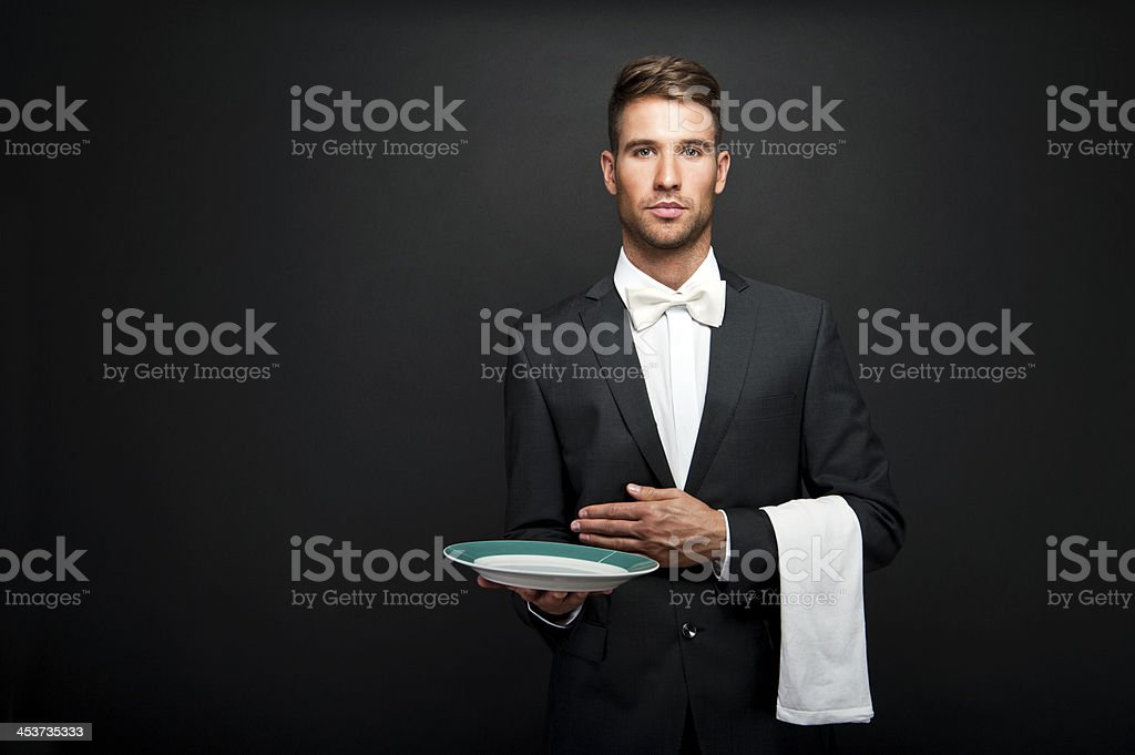 Young professional looking waiter holding a green plate stock photo