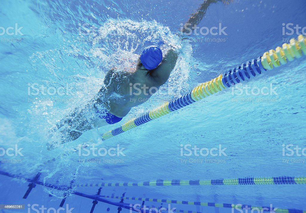 Young professional male athlete doing backstroke in swimming pool stock photo