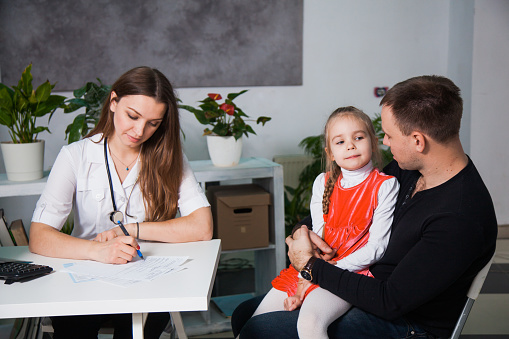 istock Young professional pediatrician writes prescriptions to a child. 1149585393