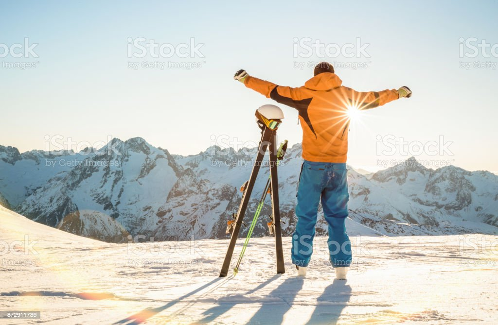 Young professional skier at sunset on relax moment in french alps ski resort - Winter sport concept with adventure guy on mountain top ready to ride down - Backlight view point with bright warm filter stock photo