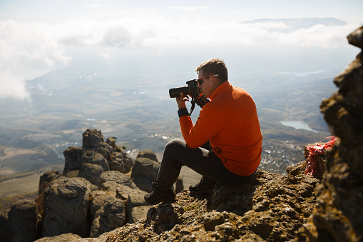 Young professional traveller man with dslr camera shooting outdoor fantastic mountain landscape. Hiker sits on a rock at the high summit and photographing above clouds