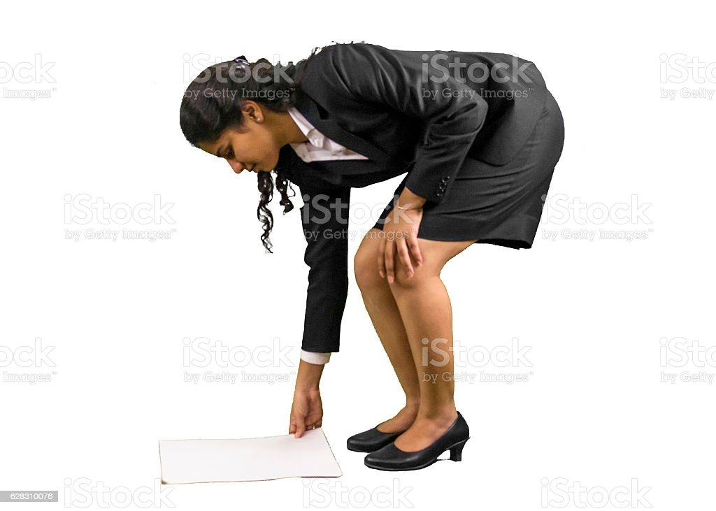 Young professional woman reaching to pick papers. stock photo