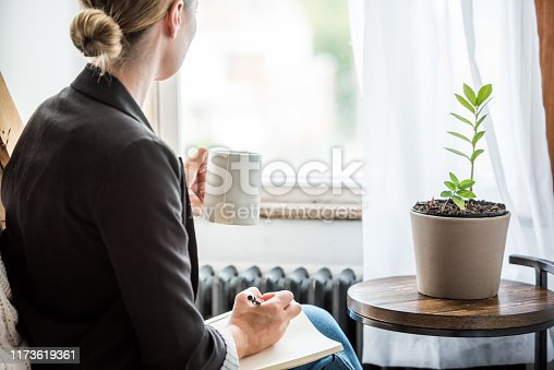 A young business woman takes a break to write in her journal about the day while sipping a cup of tea.