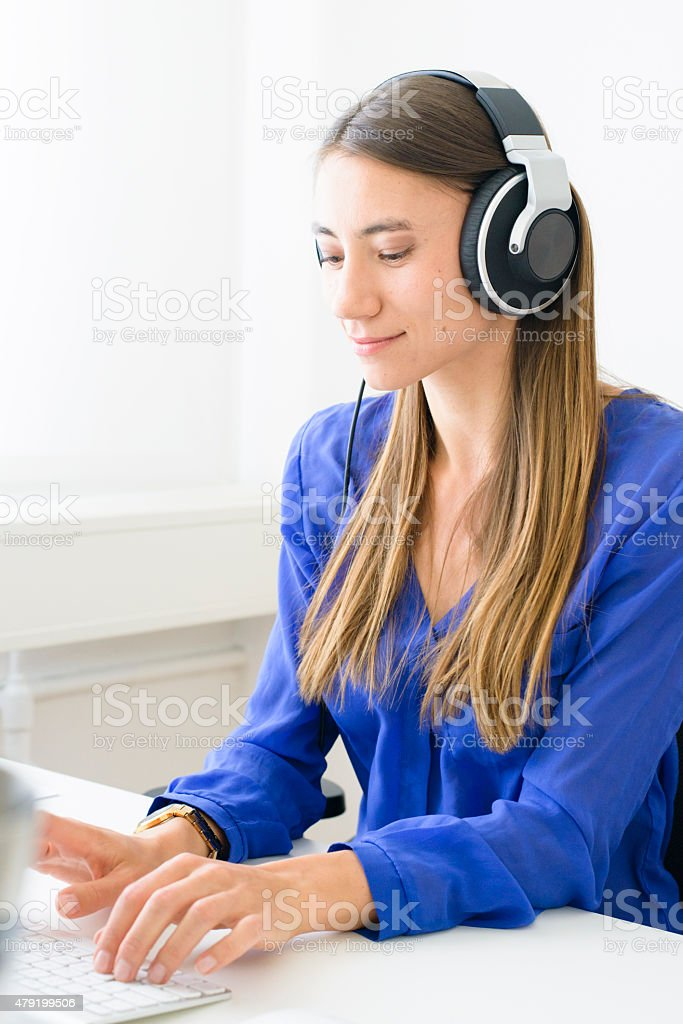 Young Professional Woman Wearing Headphones Concentrating on Computer Screen royalty-free stock photo