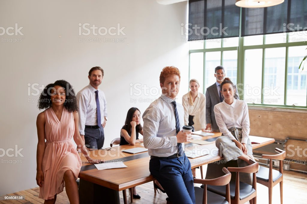 Young professionals in a meeting room looking to camera stock photo