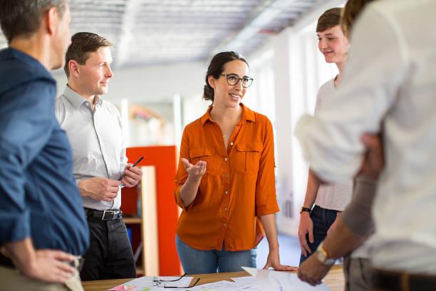 young professionals meeting around a table - deutsche frauen stock-fotos und bilder