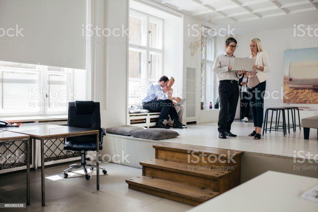 Jóvenes profesionales trabajando juntos en brillante, abrir entorno de oficina - foto de stock