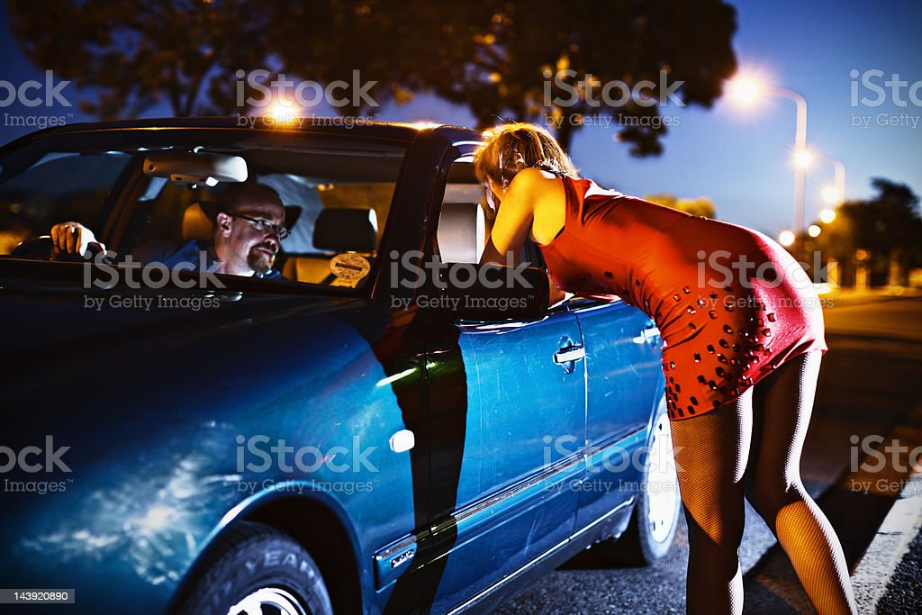Young prostitute leans into car towards sinister looking man stock photo