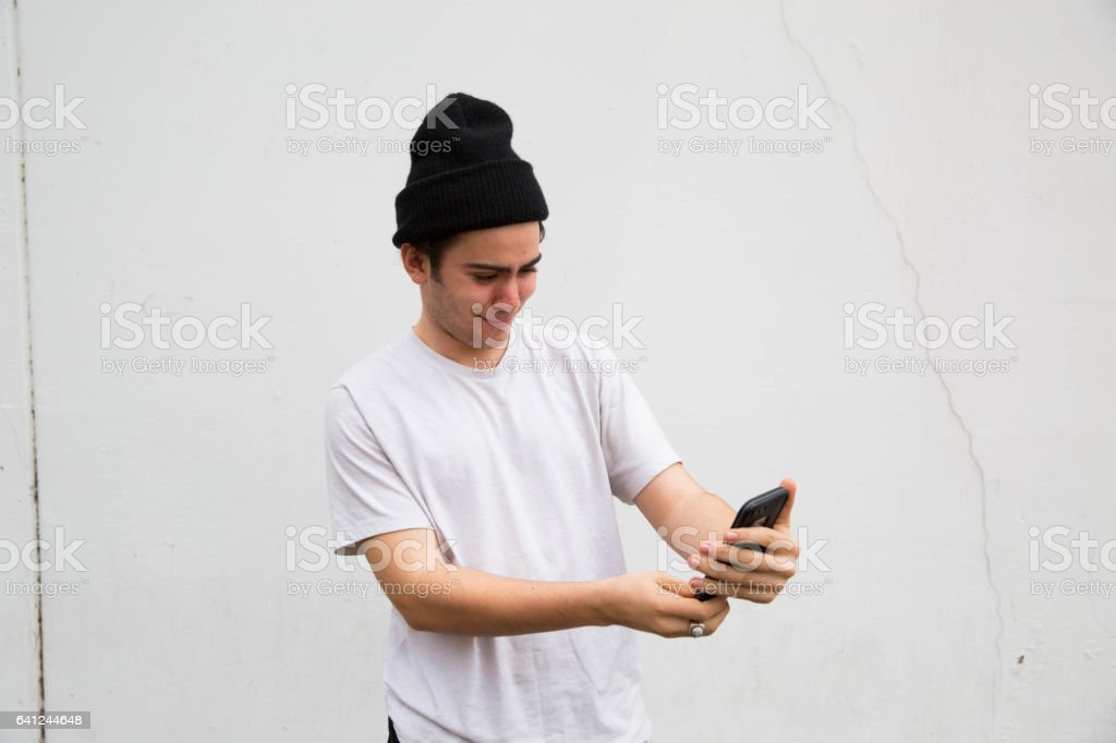 Young Punk Hispanic Italian Teen Looking At Cell Phone Taking Selfie stock photo