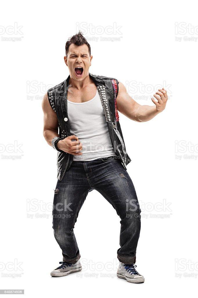 Young punk rocker playing an air guitar stock photo