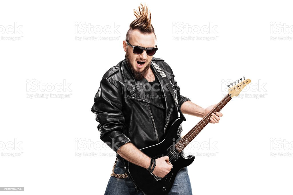 Young punk rocker playing electric guitar stock photo