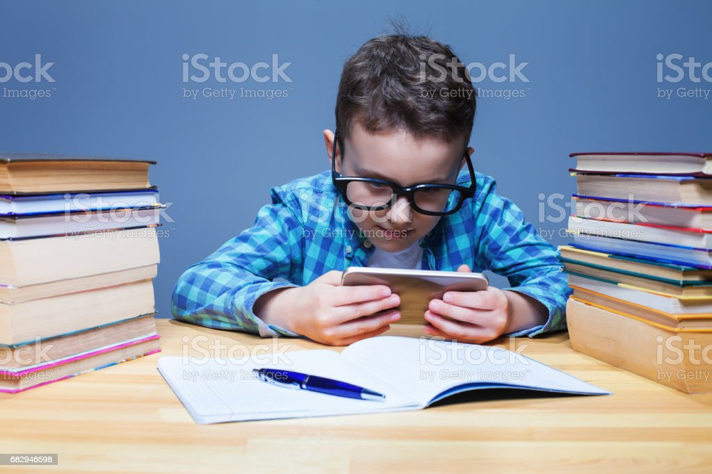 Young pupil playing on his phone in classroom royalty-free stock photo
