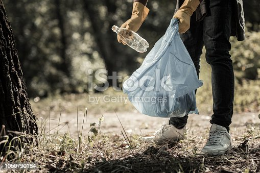 Gathering bottles. Young pupil wearing dark jeans and white sneakers gathering empty bottles in the forest