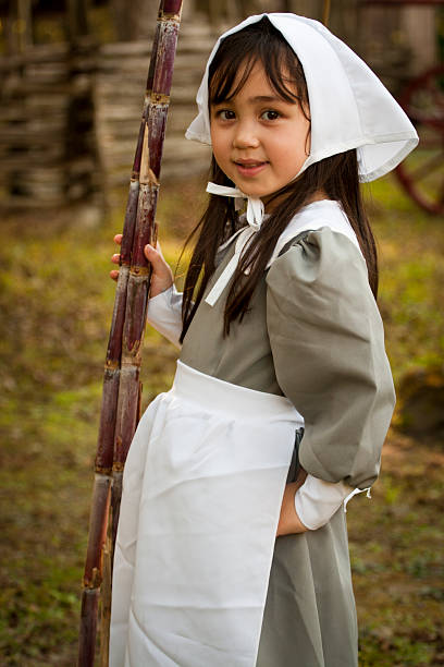 Young Puritan with Sugar Cane Cute five-year-old girl dressed as a 19th-century Puritan.Please see this slightly different version: pilgrim stock pictures, royalty-free photos & images