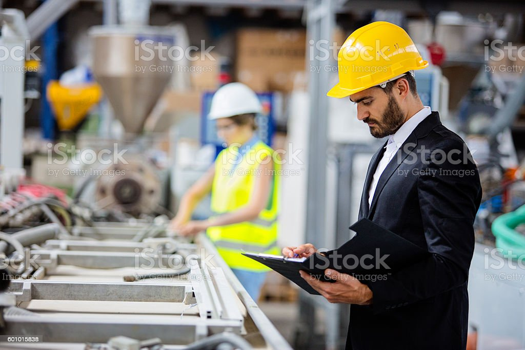 Young quality inspector checking production line Factory. Shallow DOF. Developed from RAW; retouched with special care and attention; Small amount of grain added for best final impression. 16 bit Adobe RGB color profile. Adult Stock Photo