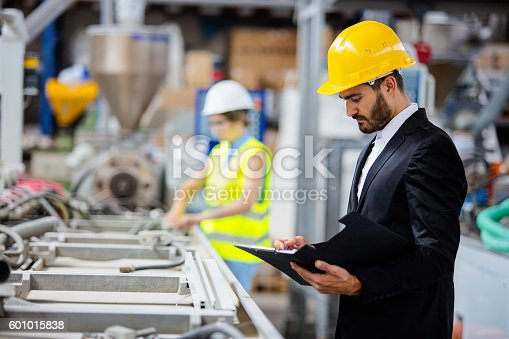 istock Young quality inspector checking production line 601015838