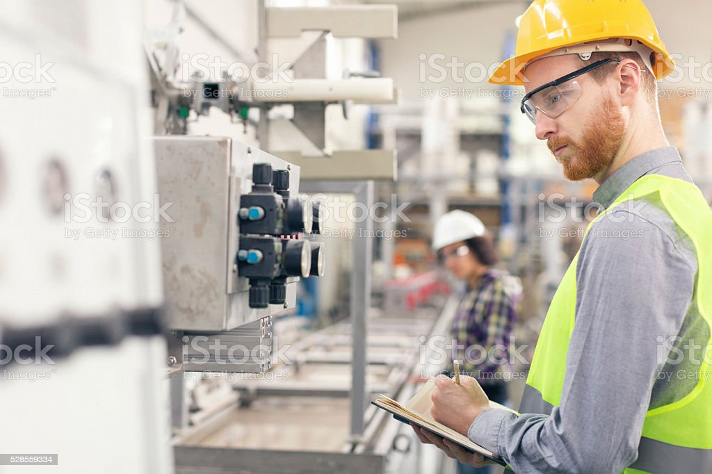 Young quality inspector taking notes in the factory stock photo
