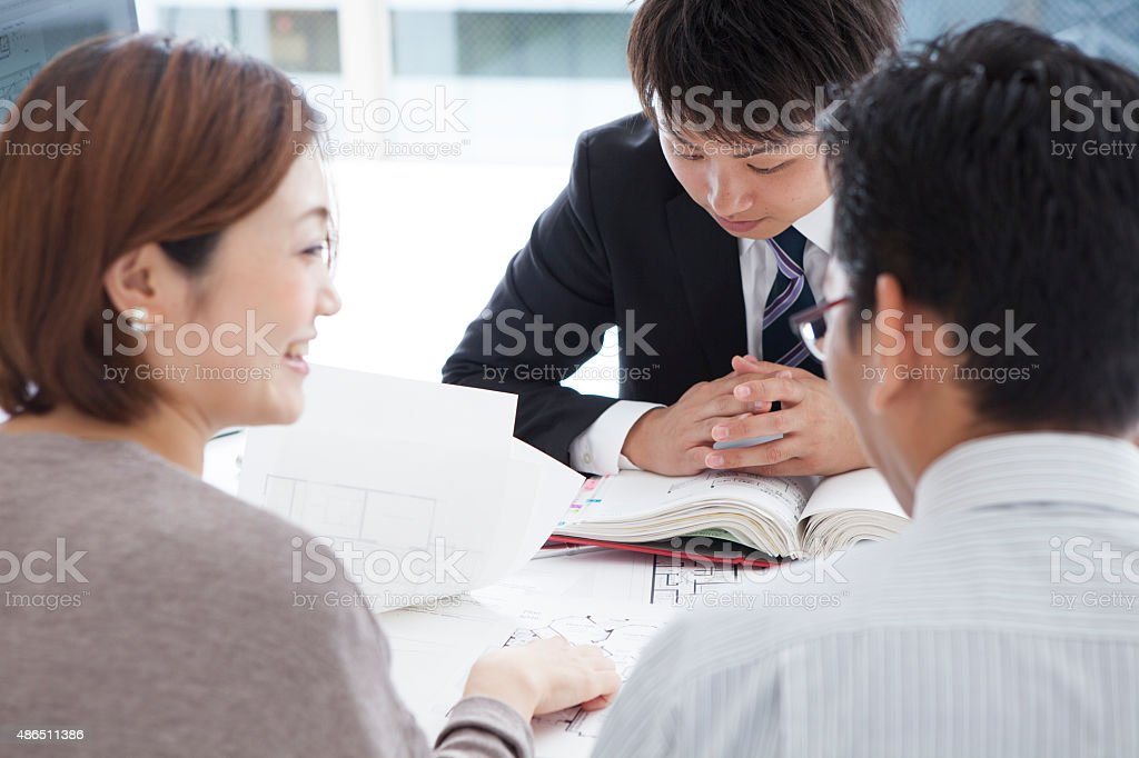 Young realtor explain lease agreement to young couple. stock photo