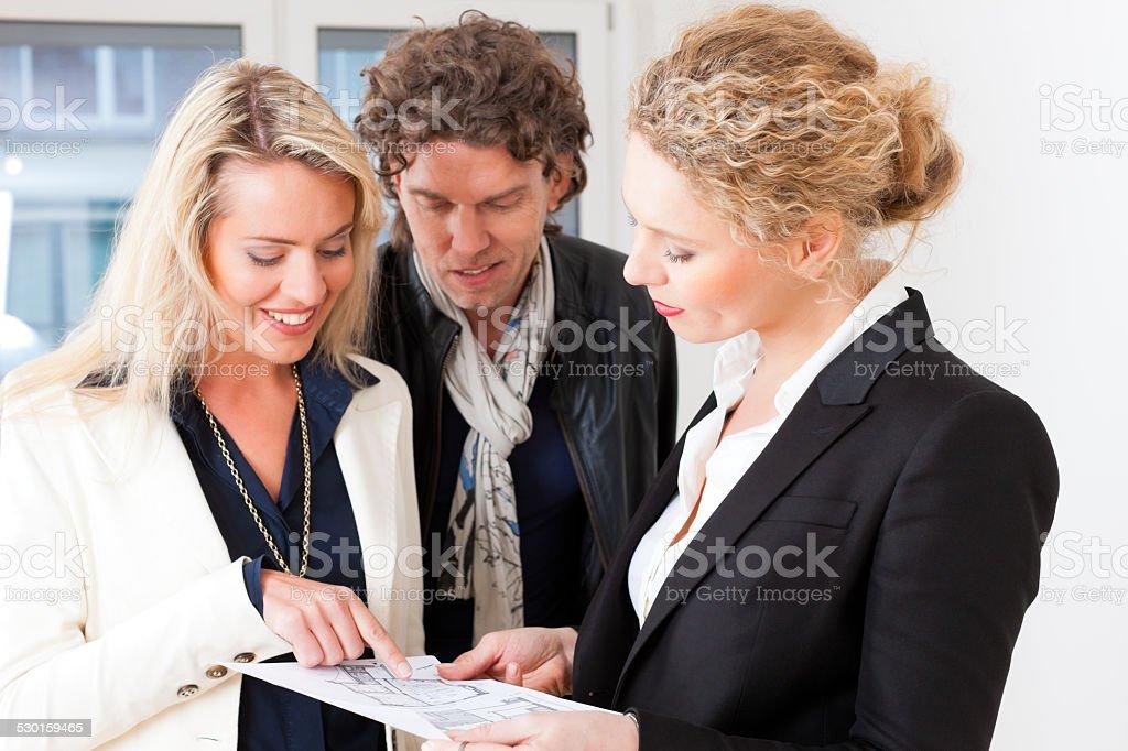 Young realtor explaining ground plan to couple stock photo