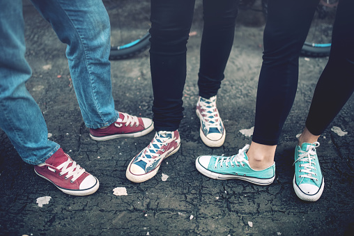 Young rebel teenagers wearing casual sneakers, walking on dirty concrete