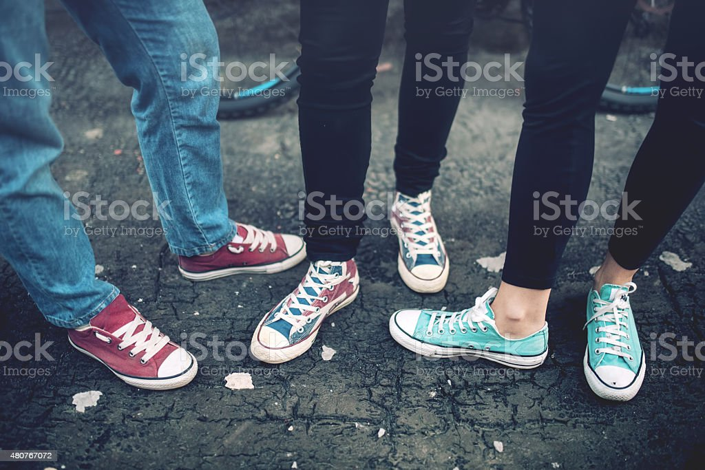 Young rebel teenagers wearing casual sneakers, walking on dirty concrete stock photo