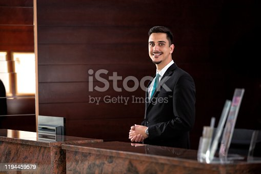 Young receptionist standing behind the front desk ready to welcome guests