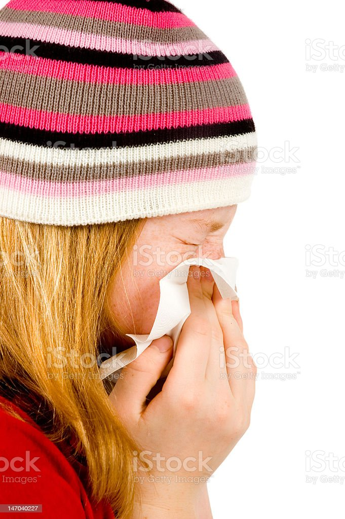 Young red girl blowing her nose - isolated on white stock photo
