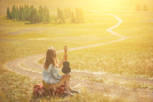 Young red hair woman play ukulele on the hill's summit. Mountain road landscape. stock photo