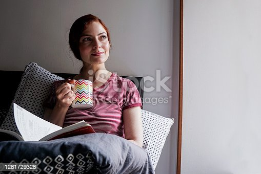 Latin woman of average age 25 years old with red hair dressed in pajamas is sitting on her bed has a cup of coffee and enjoys the moment alone as daily rituals