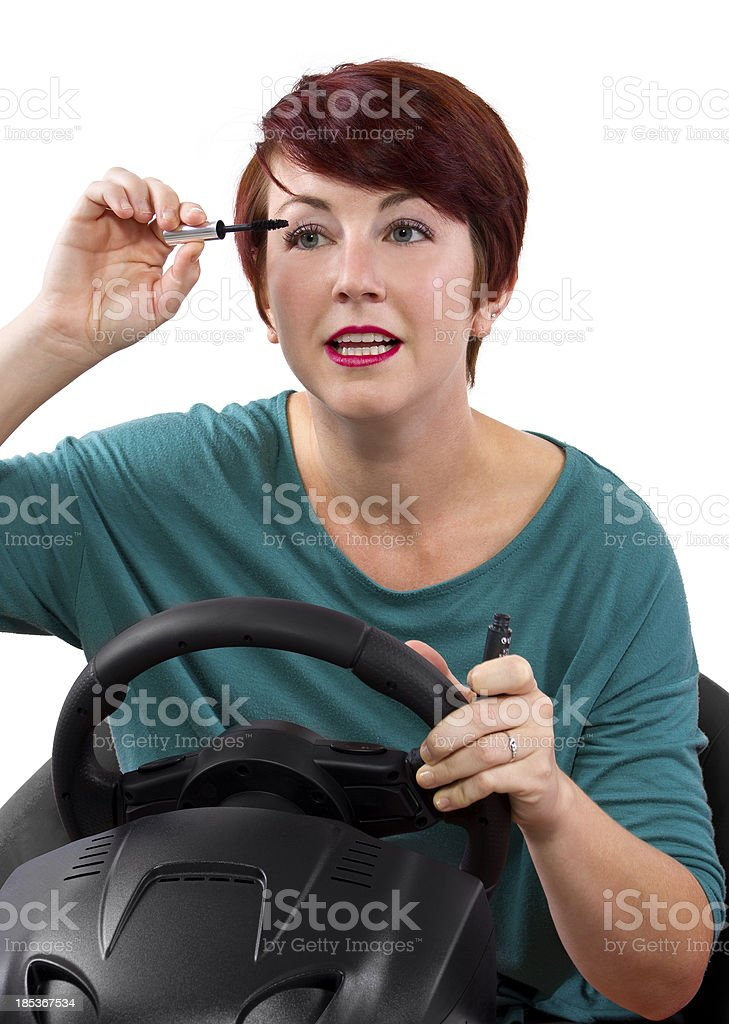 Young red head woman applying make up while driving stock photo