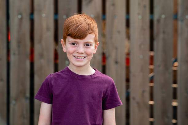 Young Redhead Boy A portrait of a boy smiling while looking at the camera. 8 9 years stock pictures, royalty-free photos & images