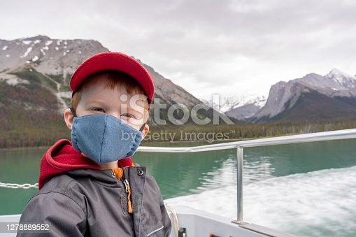 istock Young Redhead Boy Wearing a mask on tourboat at Maligne Lake, Jasper, Canada 1278889552