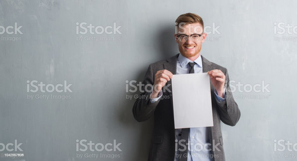 Young redhead  business man over grey grunge wall holding blank paper contract with a happy face standing and smiling with a confident smile showing teeth stock photo