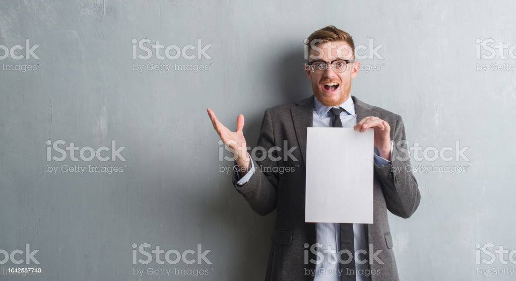 Young redhead  business man over grey grunge wall holding blank paper contract very happy and excited, winner expression celebrating victory screaming with big smile and raised hands stock photo
