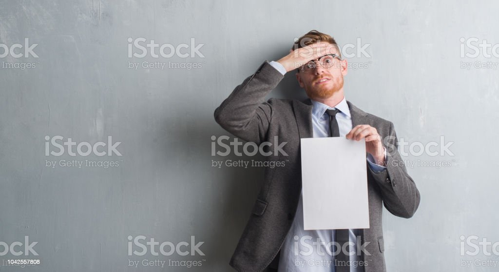 Young redhead  business man over grey grunge wall holding blank paper contract stressed with hand on head, shocked with shame and surprise face, angry and frustrated. Fear and upset for mistake. stock photo