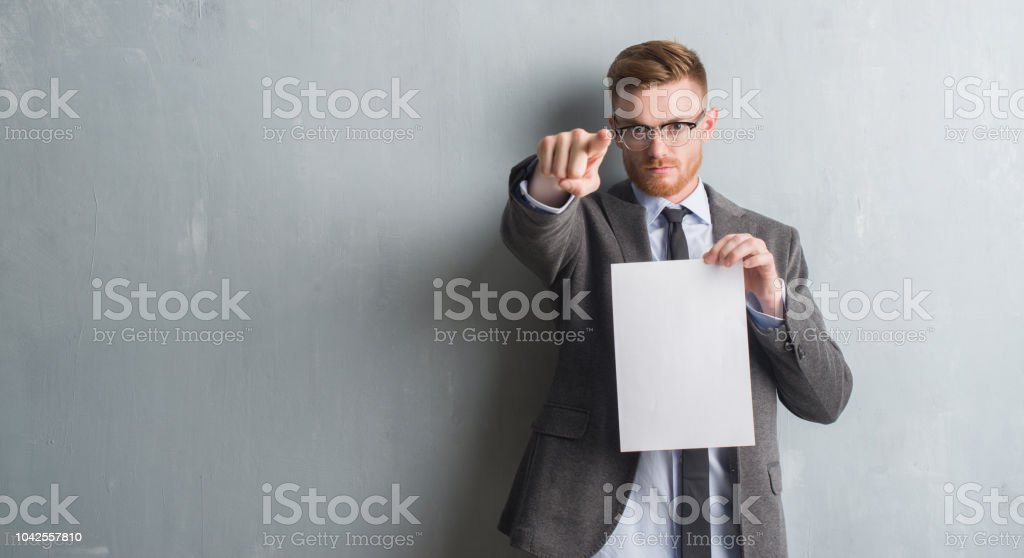 Young redhead  business man over grey grunge wall holding blank paper contract pointing with finger to the camera and to you, hand sign, positive and confident gesture from the front stock photo