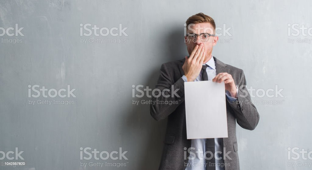 Young redhead  business man over grey grunge wall holding blank paper contract cover mouth with hand shocked with shame for mistake, expression of fear, scared in silence, secret concept stock photo