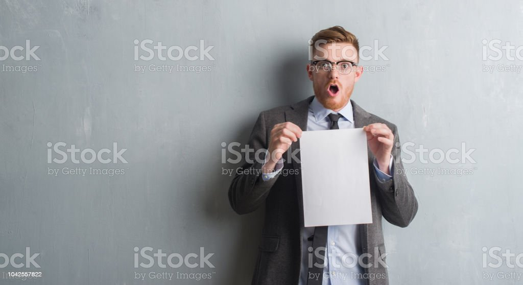 Young redhead  business man over grey grunge wall holding blank paper contract scared in shock with a surprise face, afraid and excited with fear expression stock photo