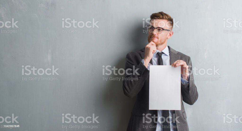 Young redhead  business man over grey grunge wall holding blank paper contract serious face thinking about question, very confused idea stock photo