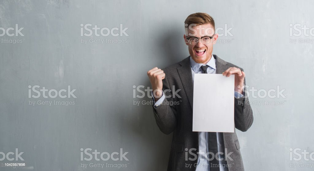 Young redhead  business man over grey grunge wall holding blank paper contract screaming proud and celebrating victory and success very excited, cheering emotion stock photo